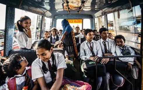Student in their uniform riding their school bus