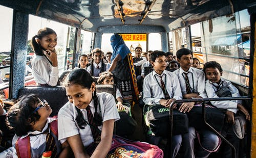 Student in their uniform riding their school bus