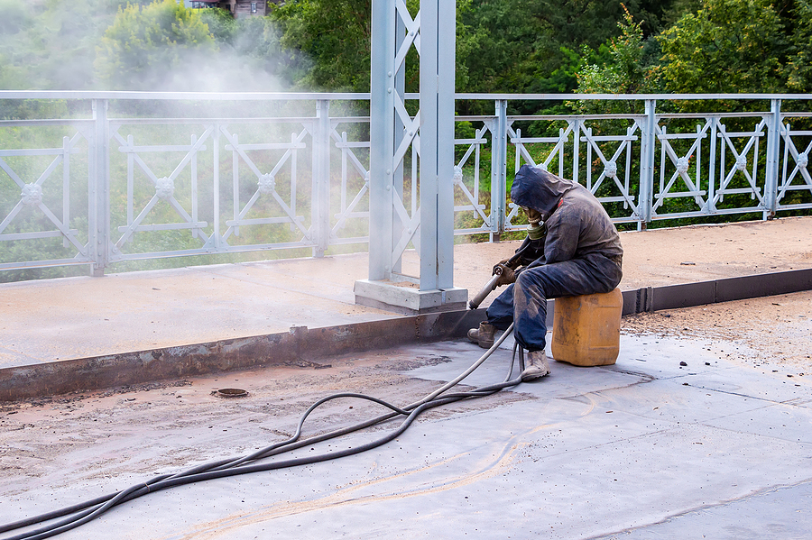 Operator of mobile sand blasting trying to remove rust
