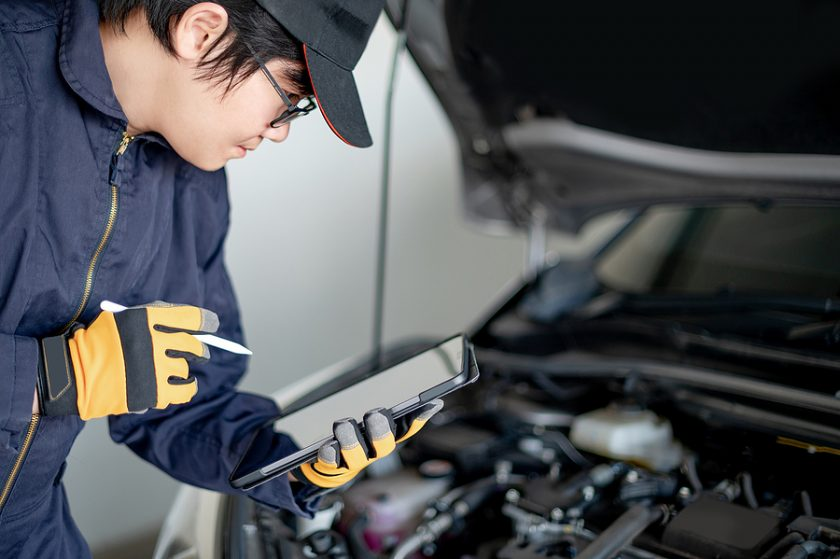 Mechanic using a workshop equipment to check the car engine